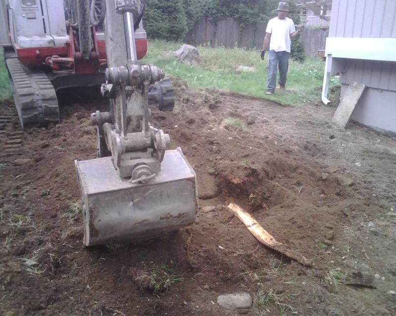 Our excavator breaking ground for a garage footing in Seattle.